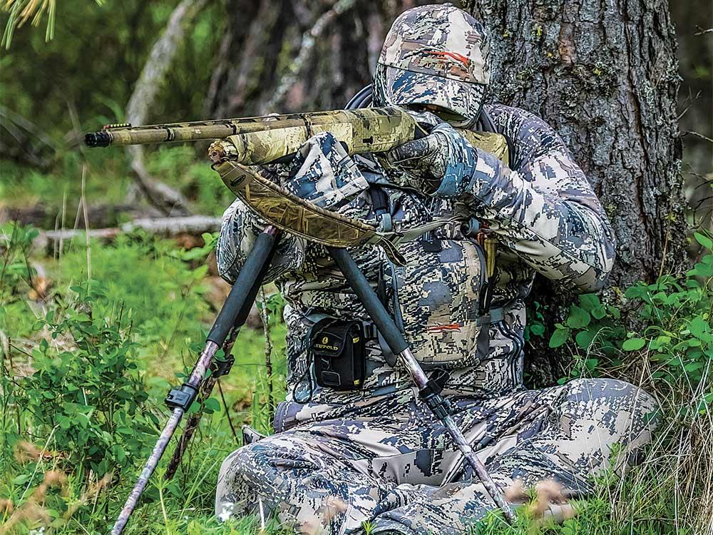 hunter using tripod to aim shotgun