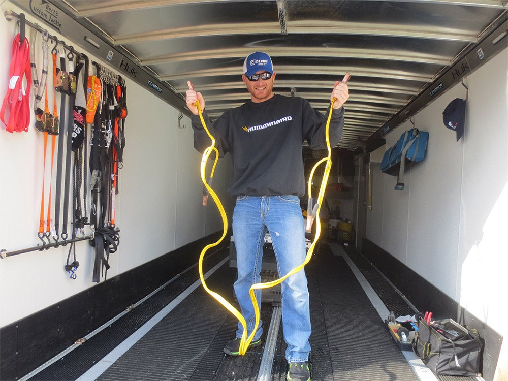 man holding up yellow jumper cables