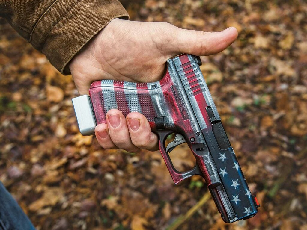 man holding a handgun painted with the american flag