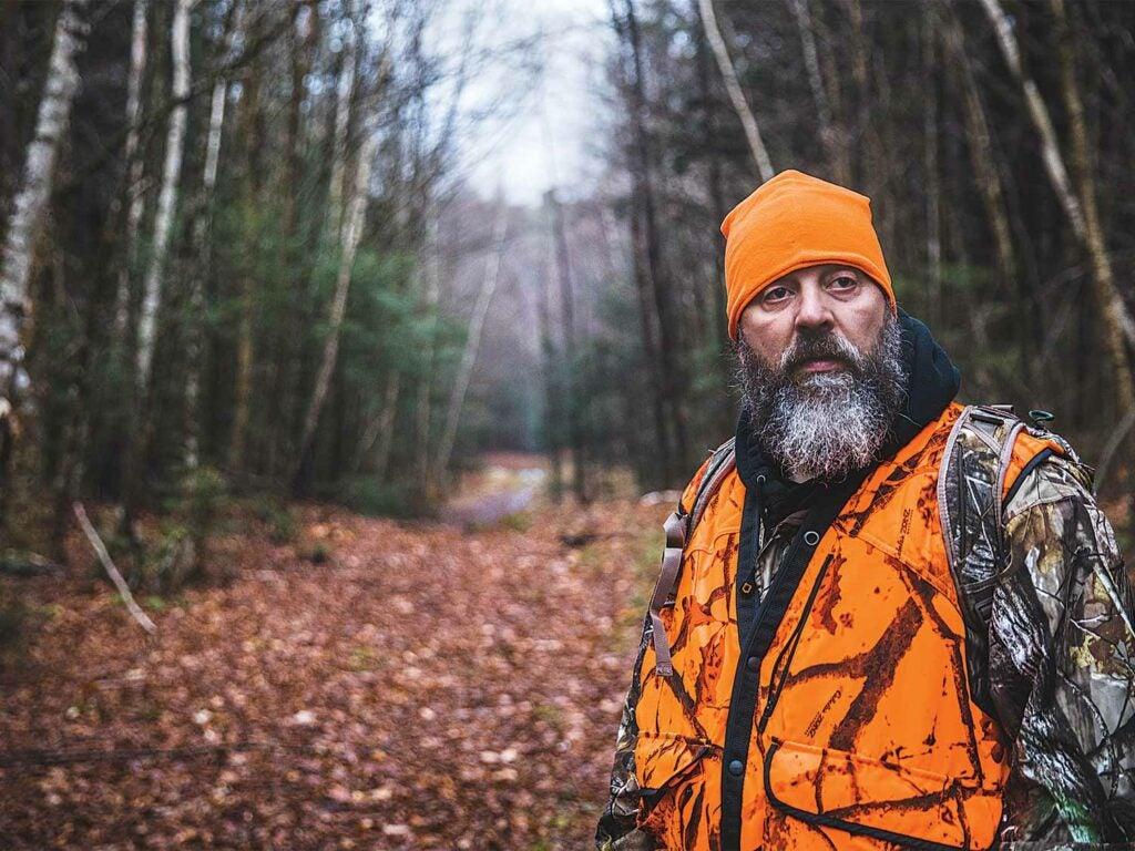 hunter in orange standing in the woods