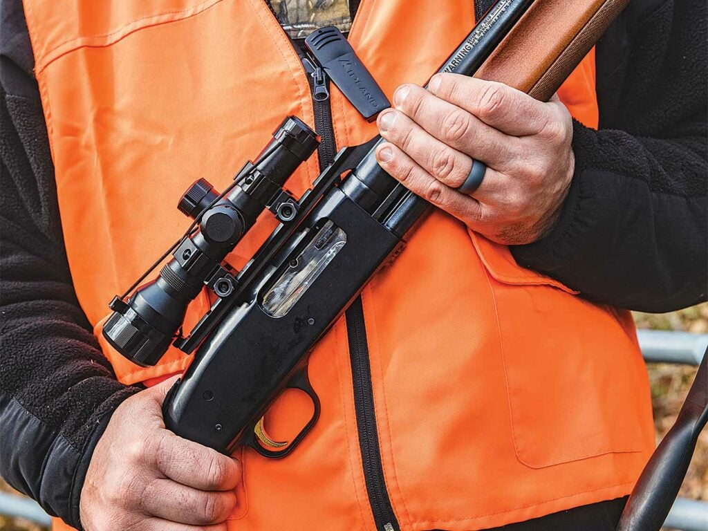 a hunter wearing an orange vest and holding a rifle