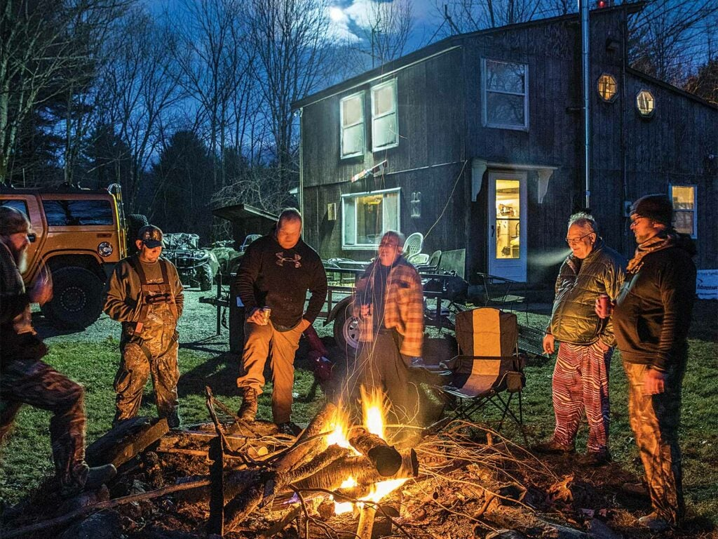 group of hunters standing beside a fire at deer camp during the night
