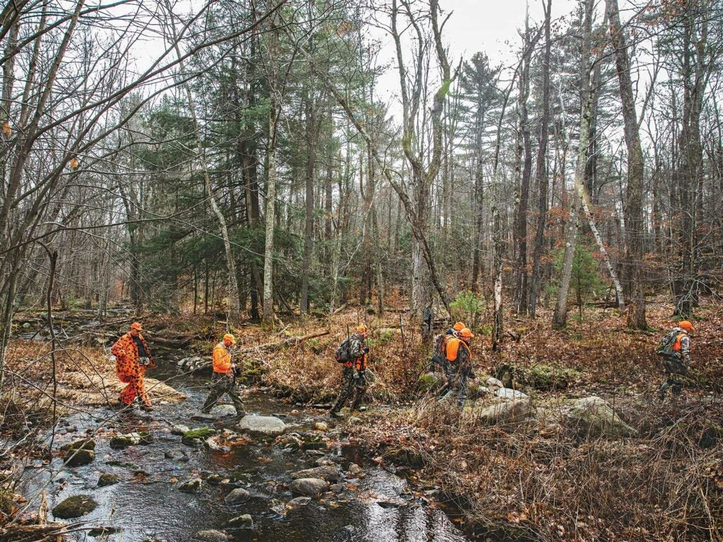 four hunters crossing a creek in the woods