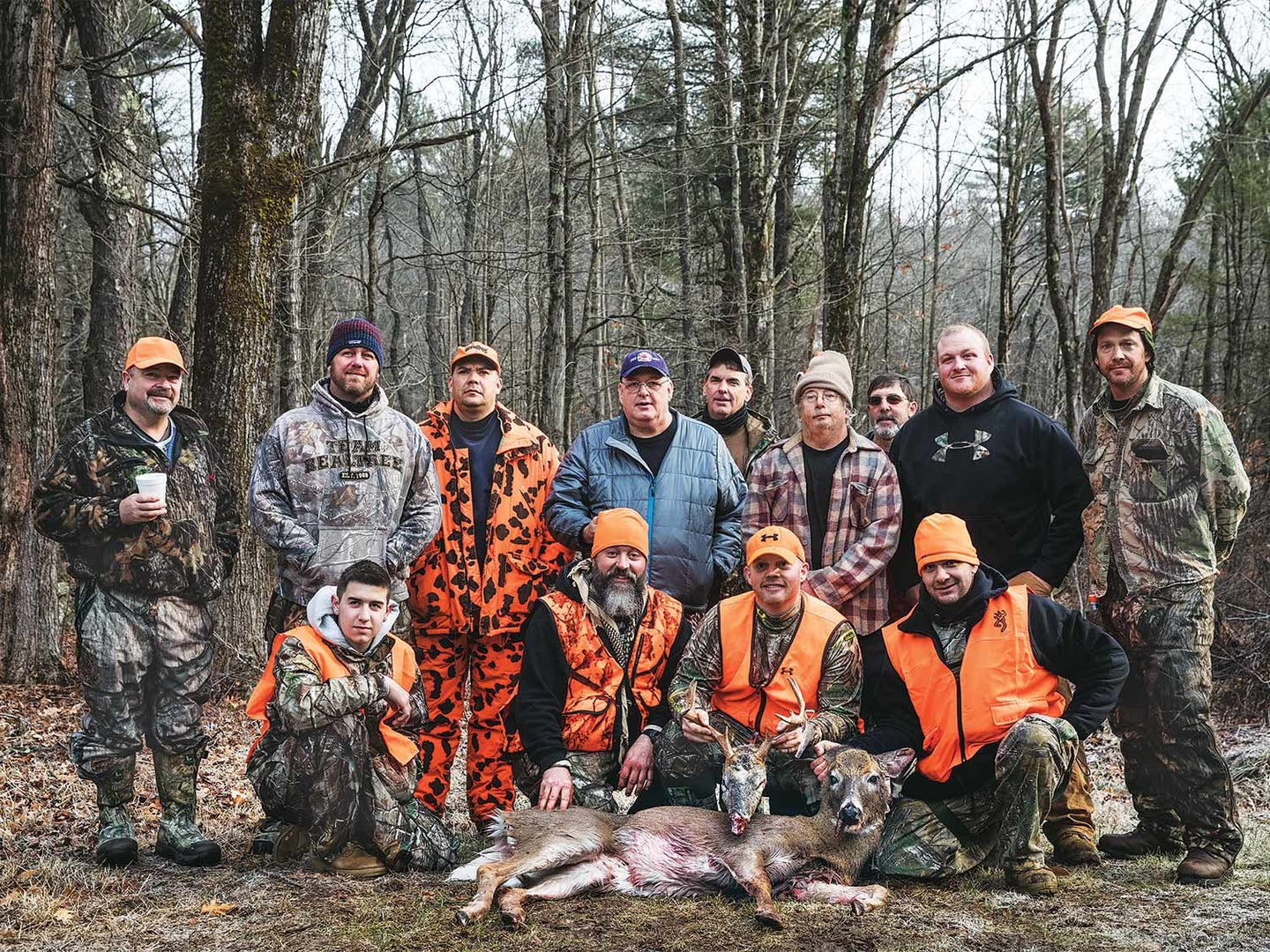 group of male hunters standing over a deer