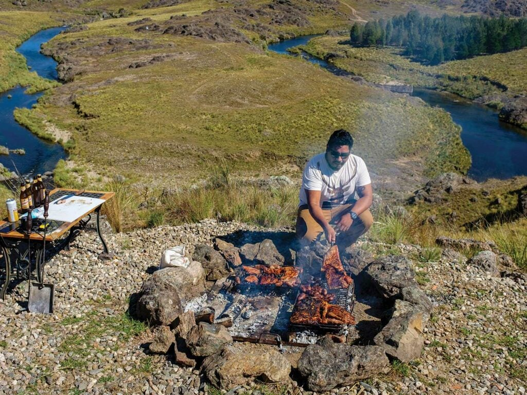 man cooking red stag on a campfire on the hillside of Argentina