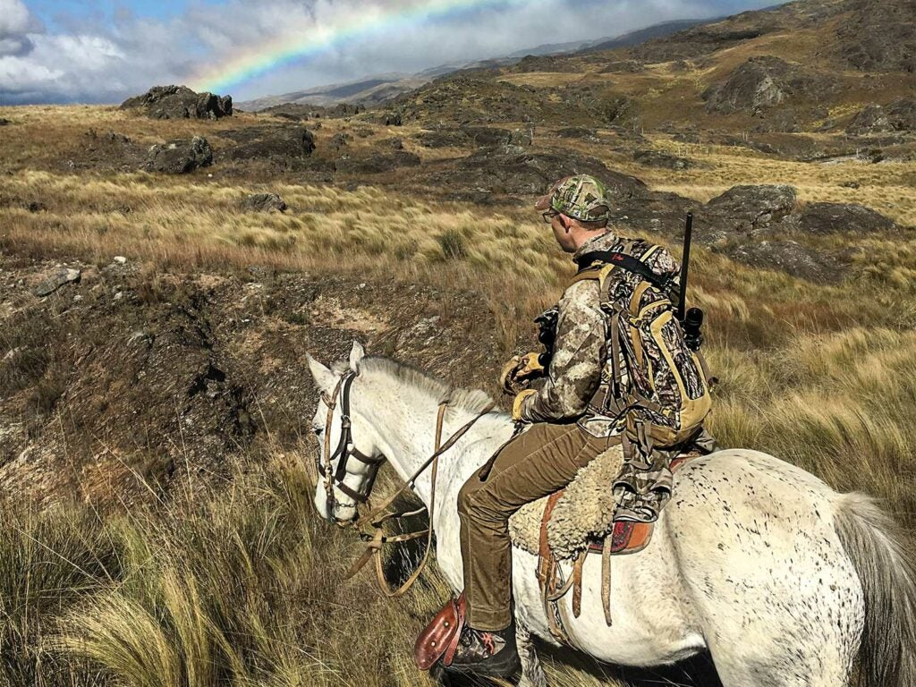 hunter riding horseback through Argentina hillsides