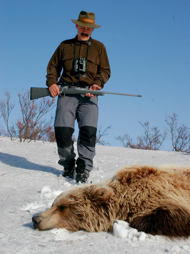hunter and dead grizzly bear in the snow