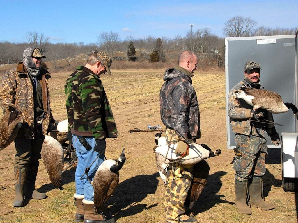 four bird hunters holding goose decoys