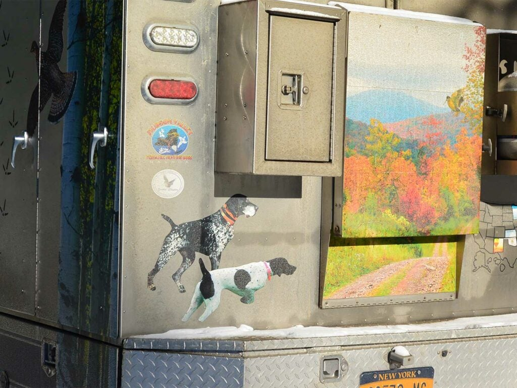 paintings of hunting dogs and landscape on the side of a truck