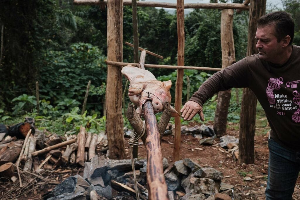man roasting pig on a spit