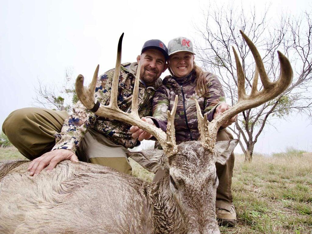 two hunters kneeling behind giant buck antlers