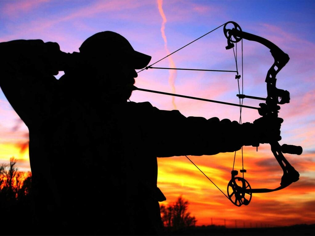 silhouette of a bowhunter aiming a compound bow