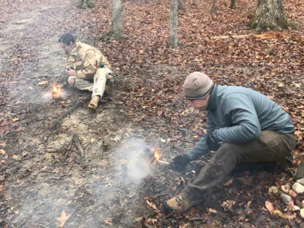 two men practicing building a fire in the woods