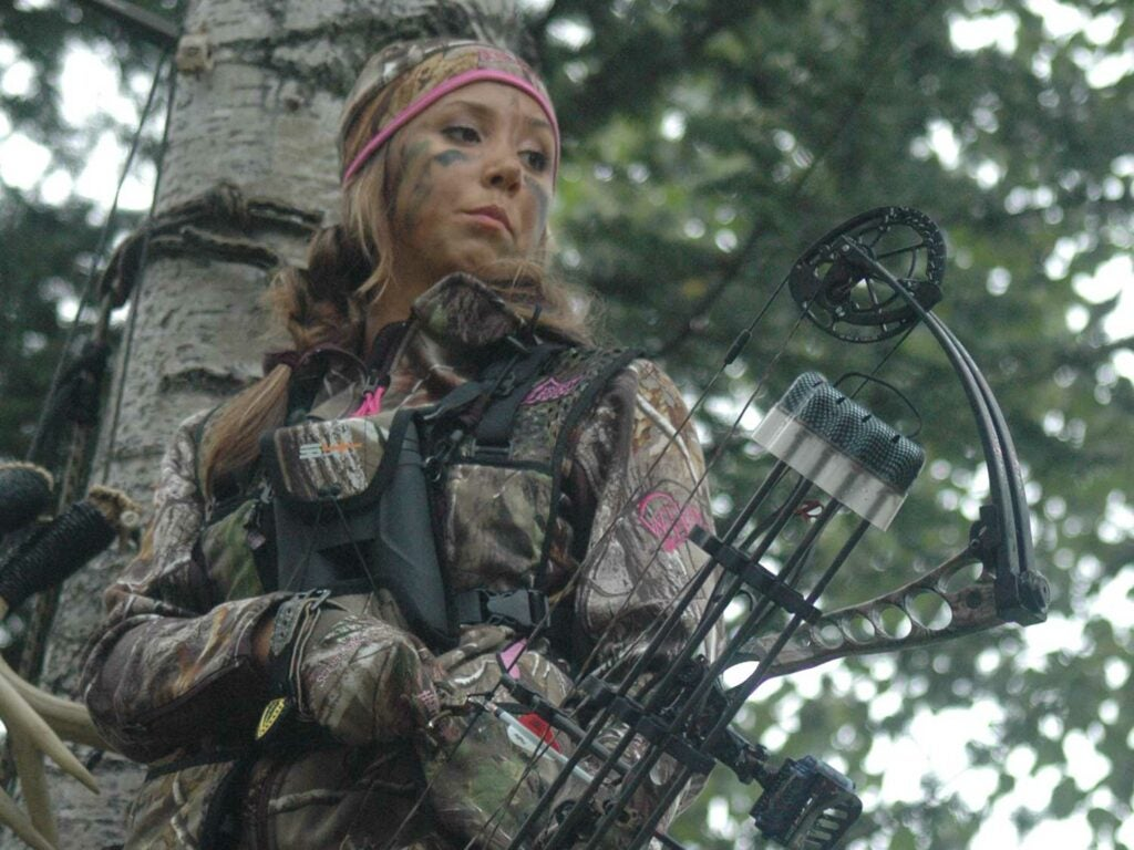 female hunter holding a compound bow