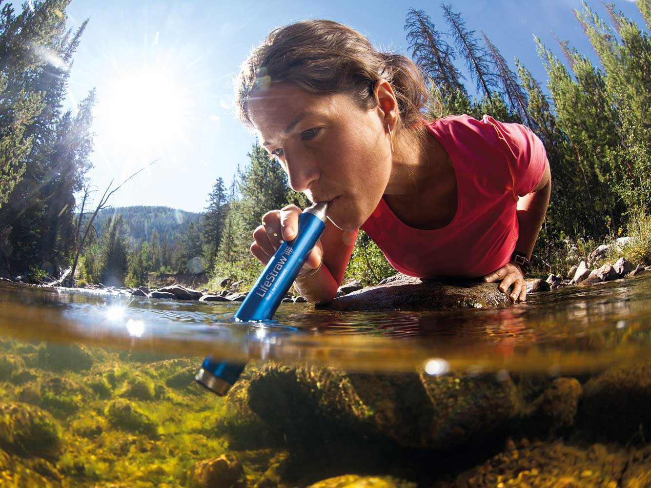 woman using lifestraw to drink water from river