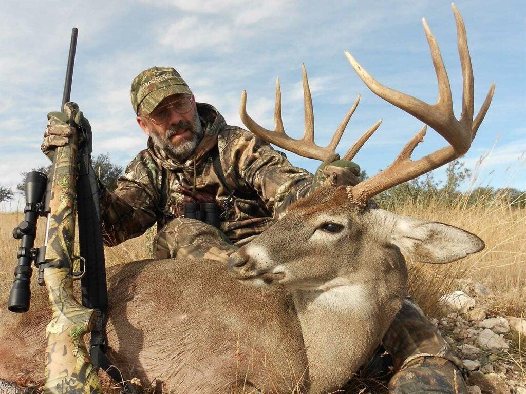 hunter kneeling behind whitetail buck