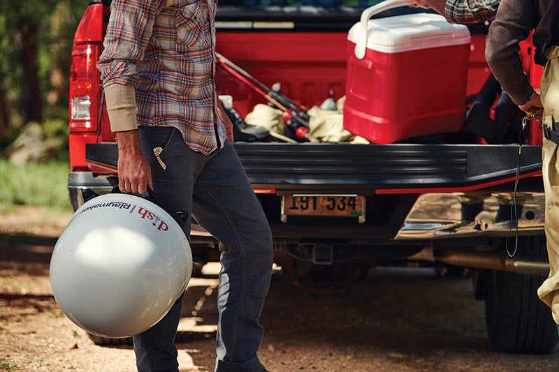man carrying dish playmaker behind a truck