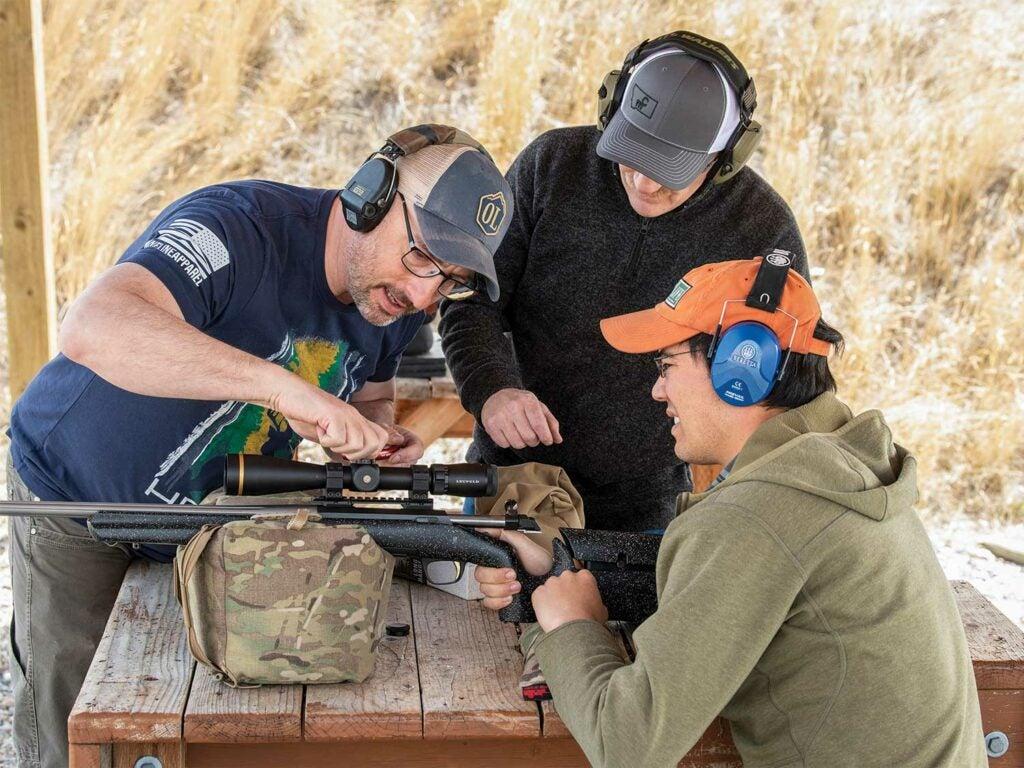 men adjusting rifle scope on rifle