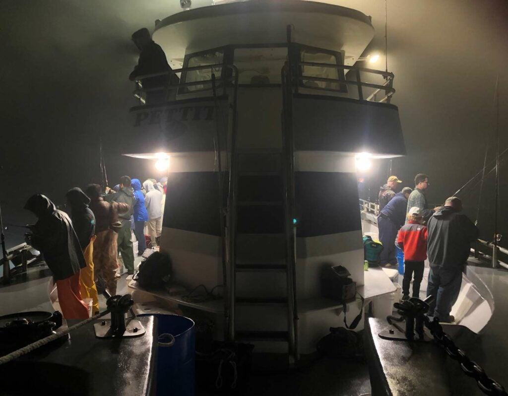 several fisherman fishing at night