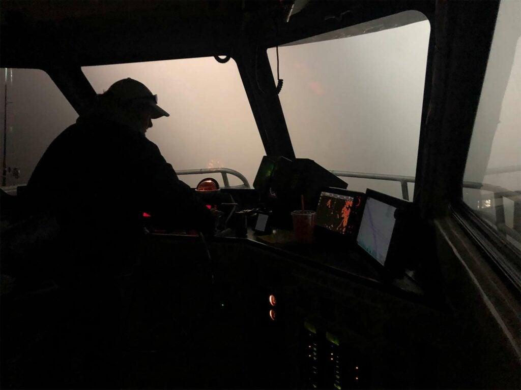 boat captain navigating boat through fog