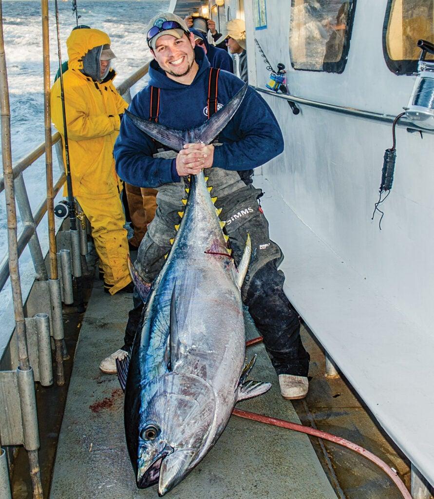 Jimmy Fee holding a giant bigeye tuna on the deck of a boat