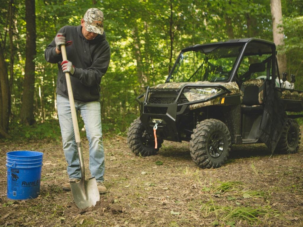 man digging with shovel in a food plot