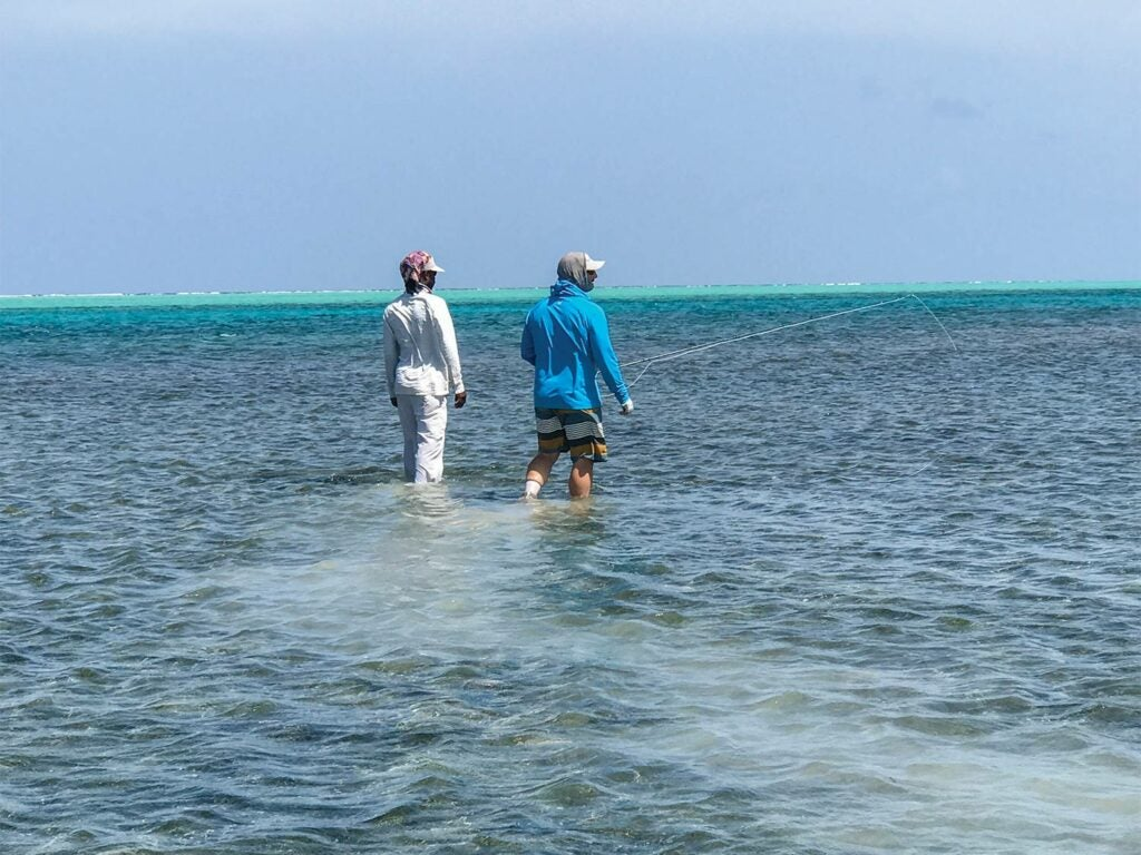 two anglers walking through the saltwater Turneffe Flats