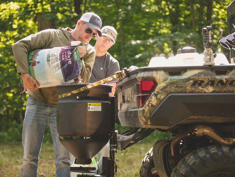 men adding fertilizer to utv dispenser