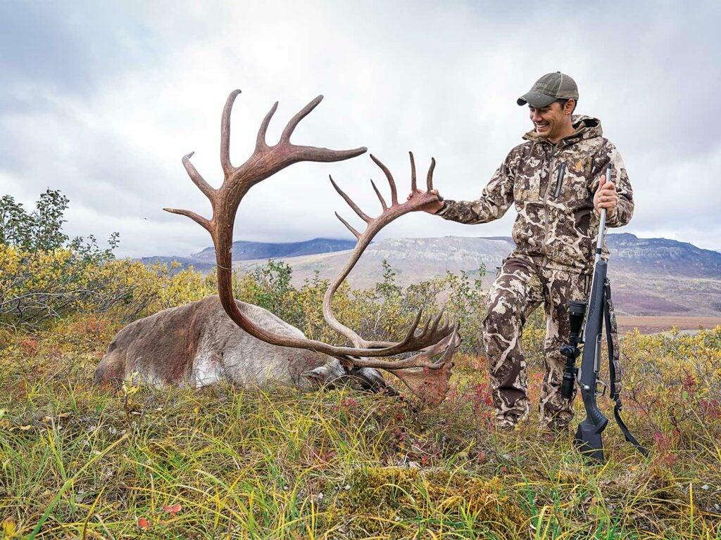Alex Robinson standing by an alaskan caribou