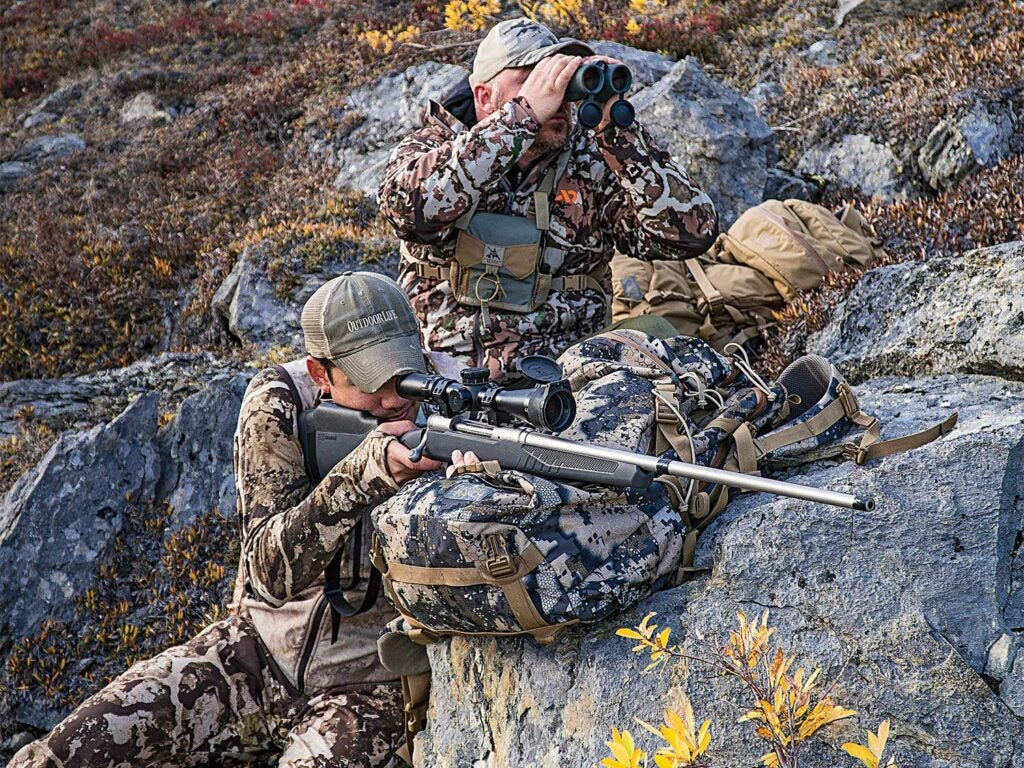hunter aiming a rifle while another looks through binoculars