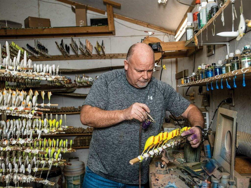 a man painting yellow custom crankbaits