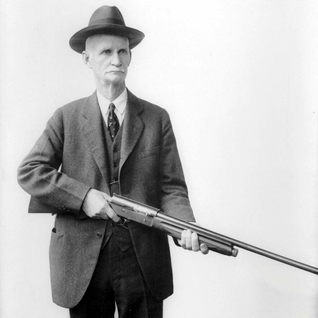 john moses browning holding an automatic-5 shotgun