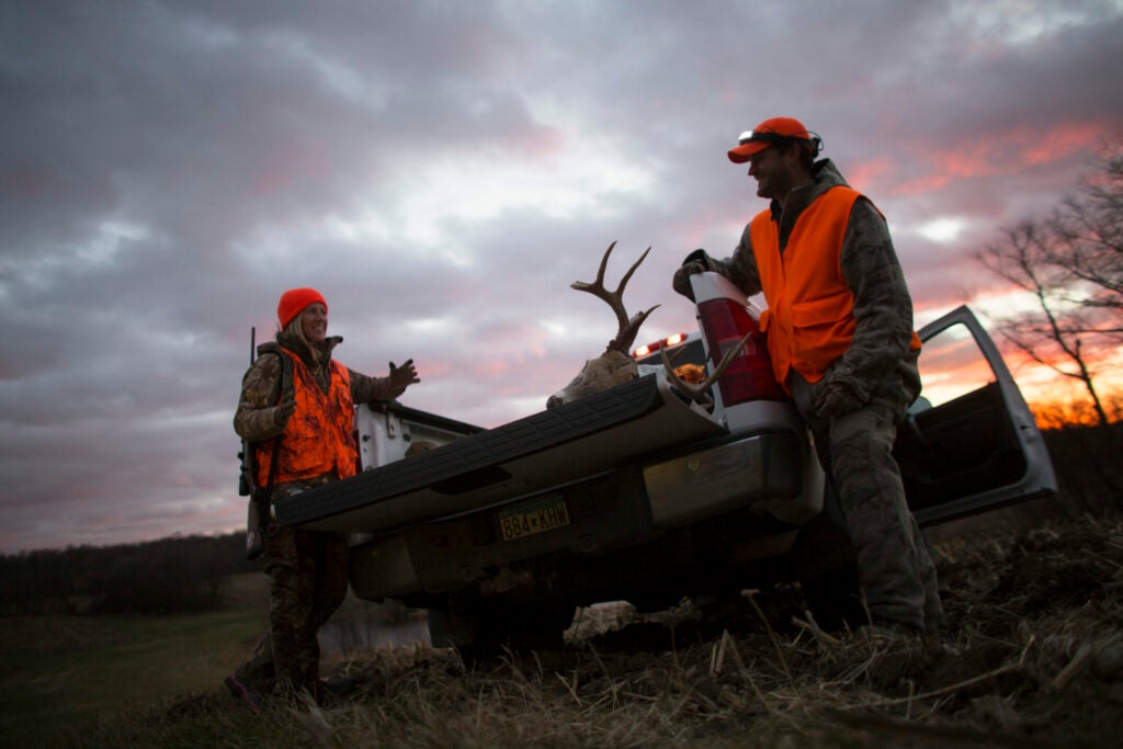 hunters with whitetail in back of truck