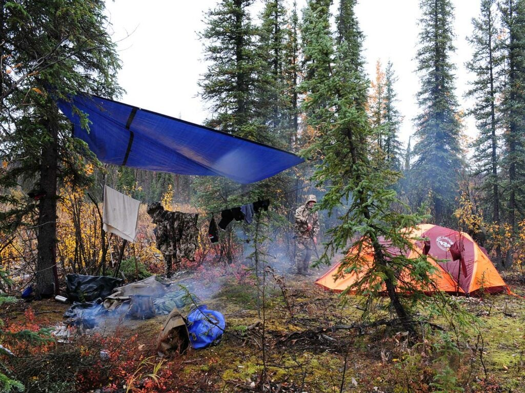 a backcountry hunting camp with a tarp over the kitchen