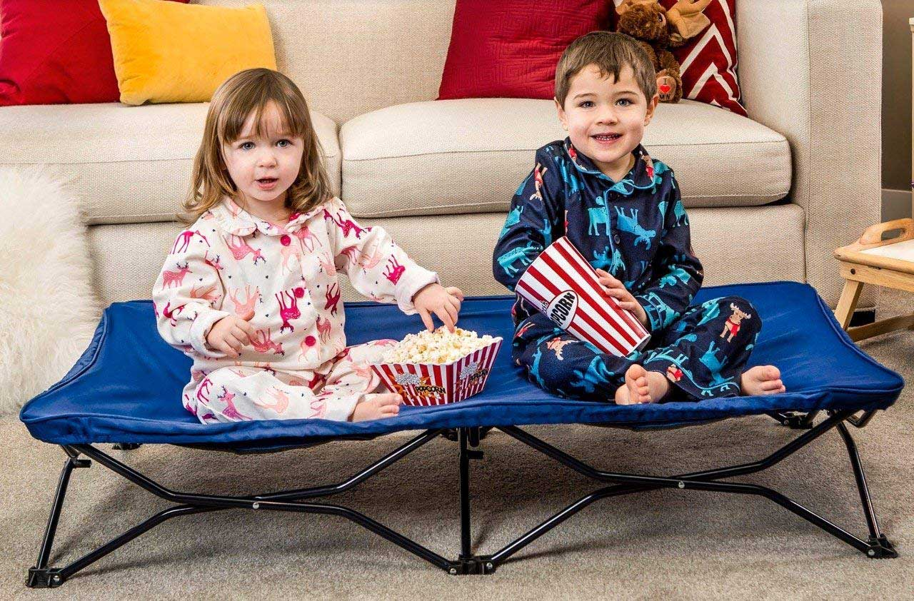 two children sitting on a portable cot