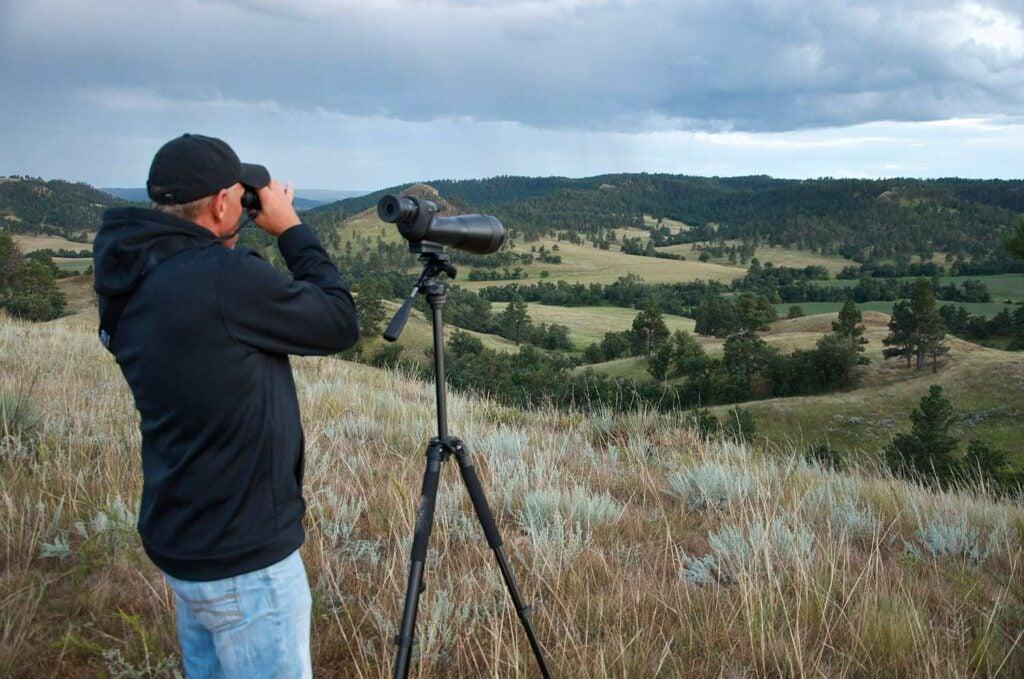 a hunter using binoculars and spotting scopes