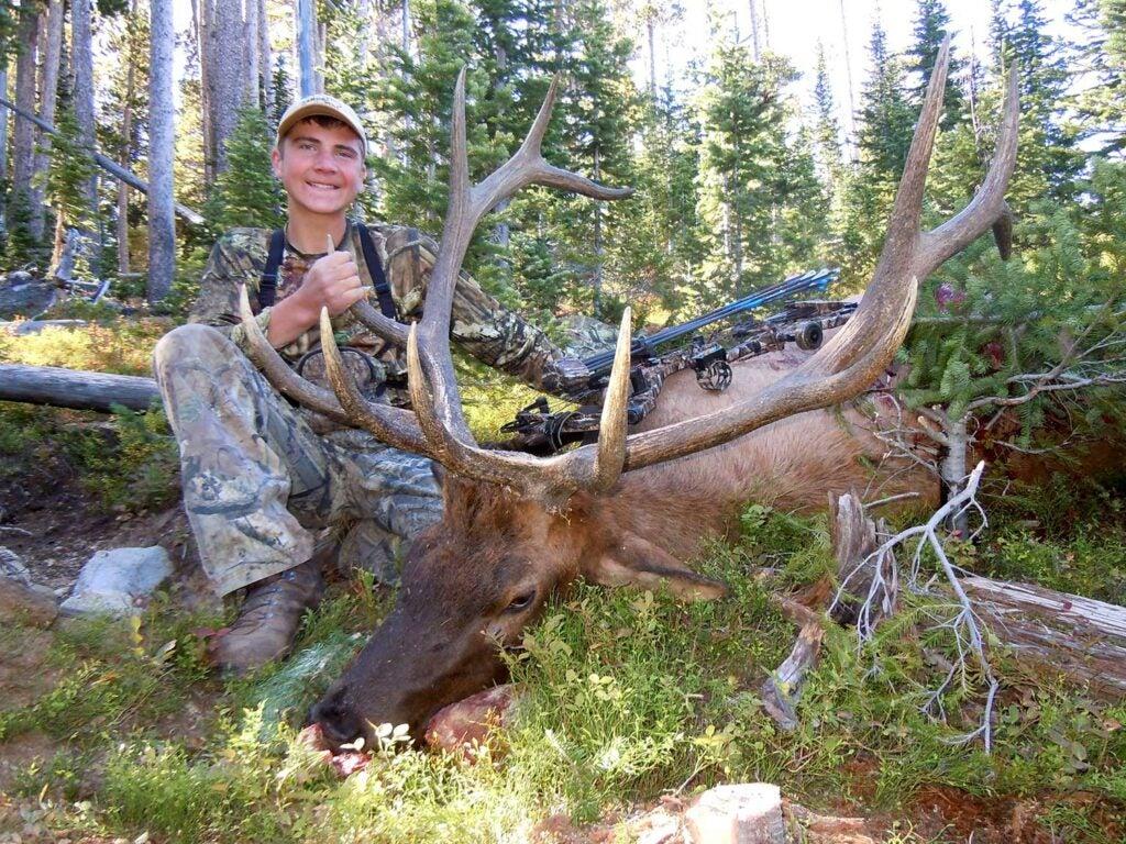 young hunter kneeling beside giant elk