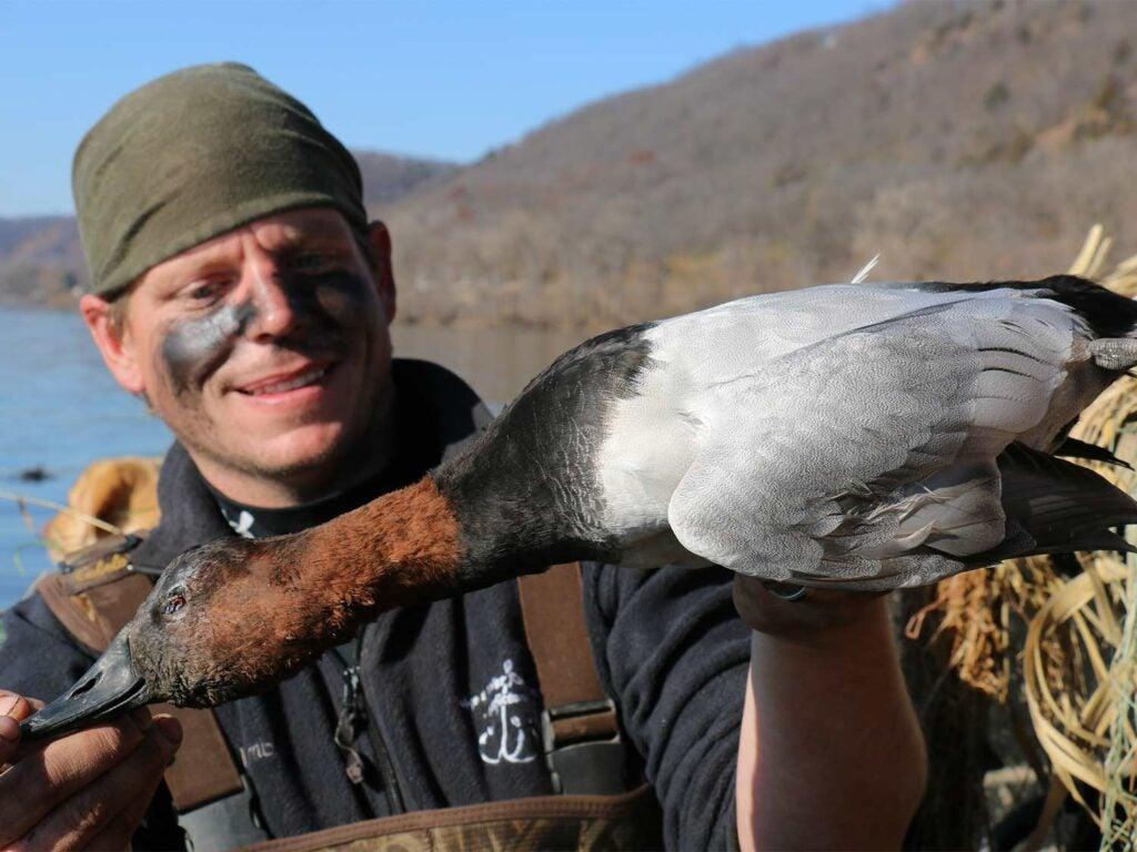 hunter holding up canvasblack duck
