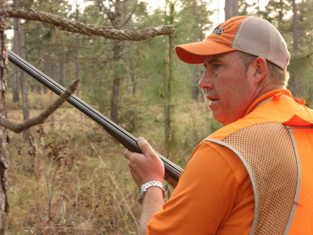man in orange holding a shotgun