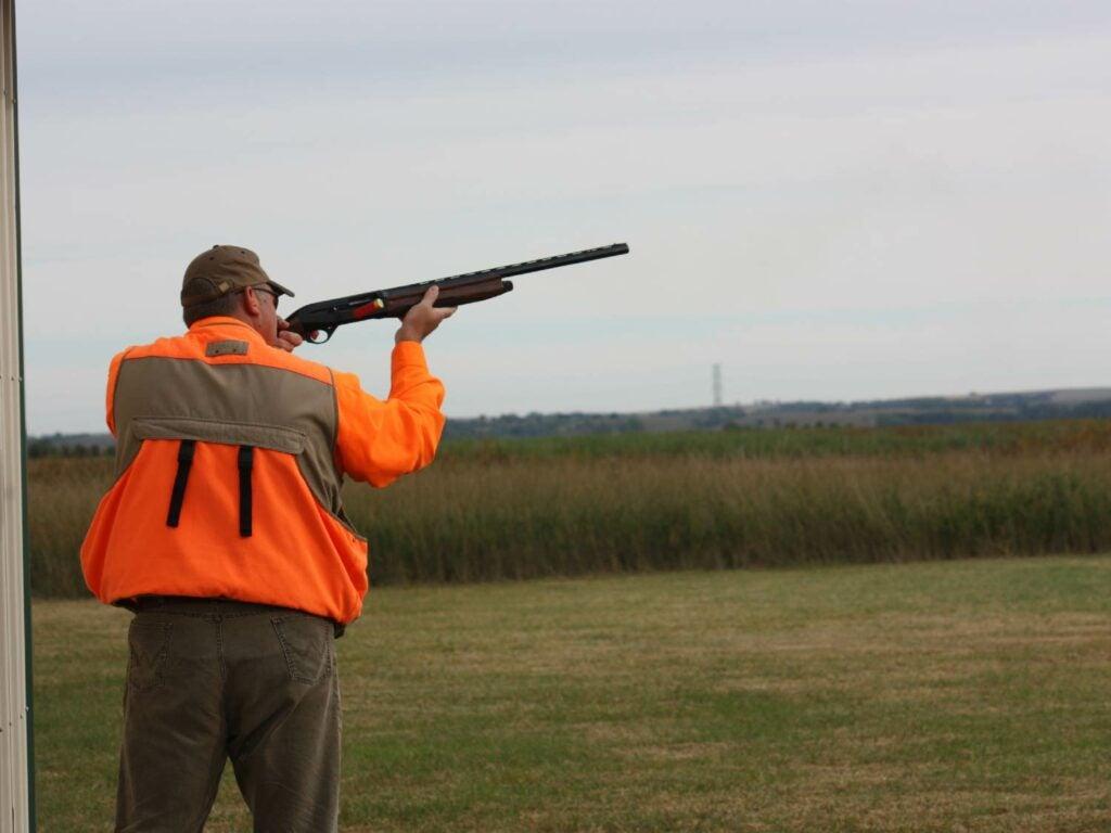 man aiming a shotgun in a field