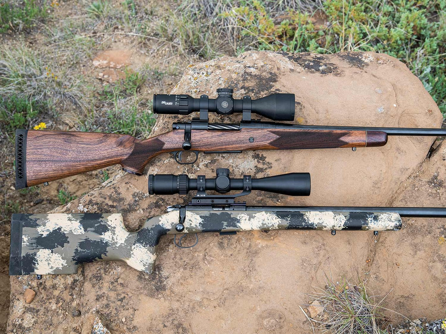 two rifles with rifle scopes