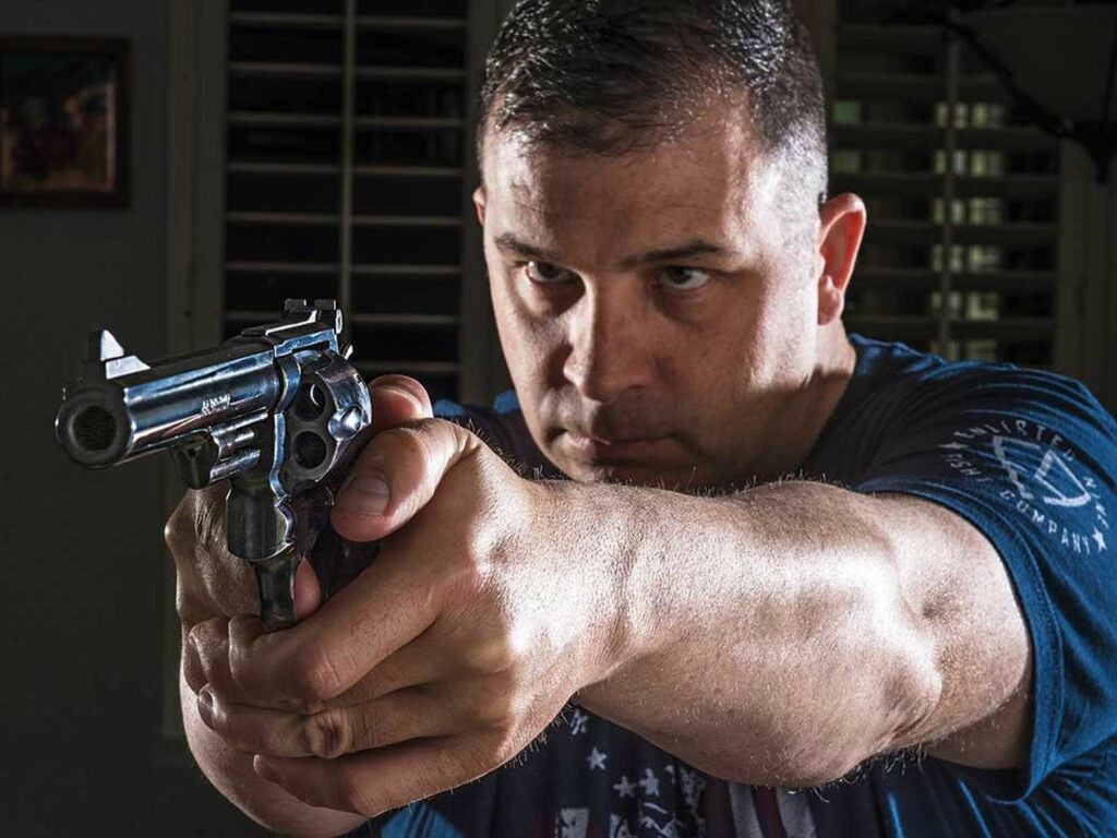 A man aims a revolver for personal defense.