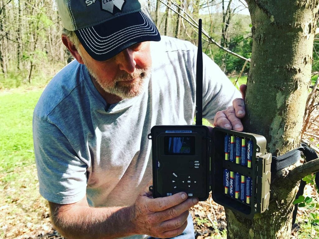man installing trail cam on a tree