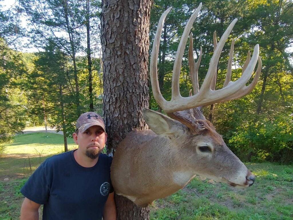 stanley suda standing beside a deer head mounted on a tree