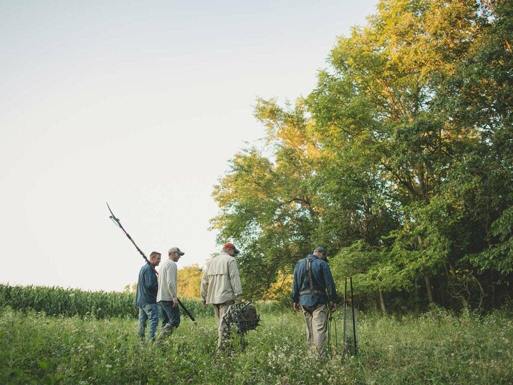 four men standing in a food plot field