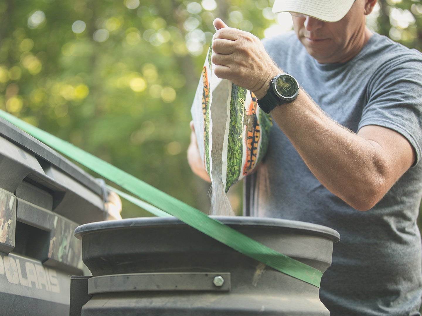 man pouring clover seeds into a seed distributor