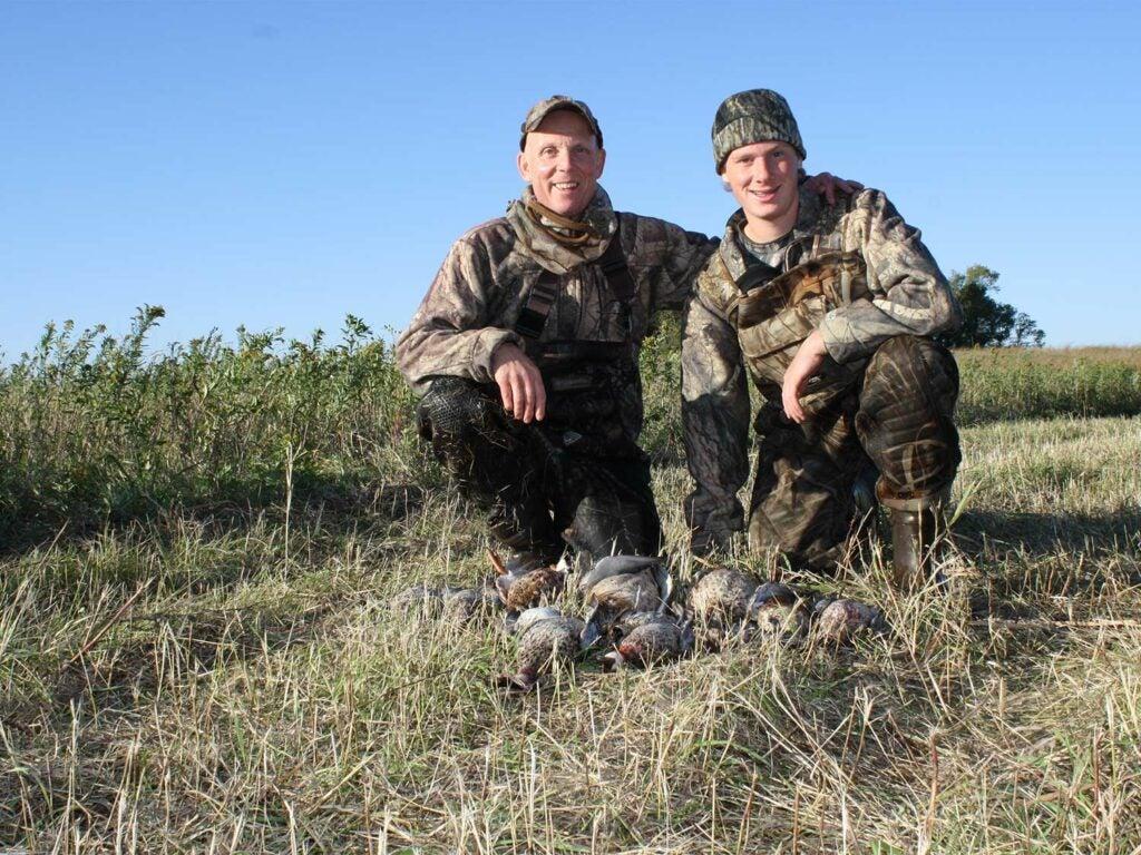 two hunters kneeling behind ducks