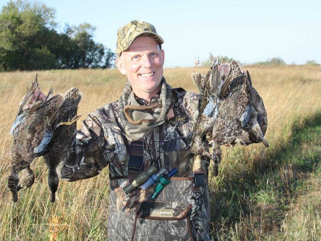 hunter holding up ducks