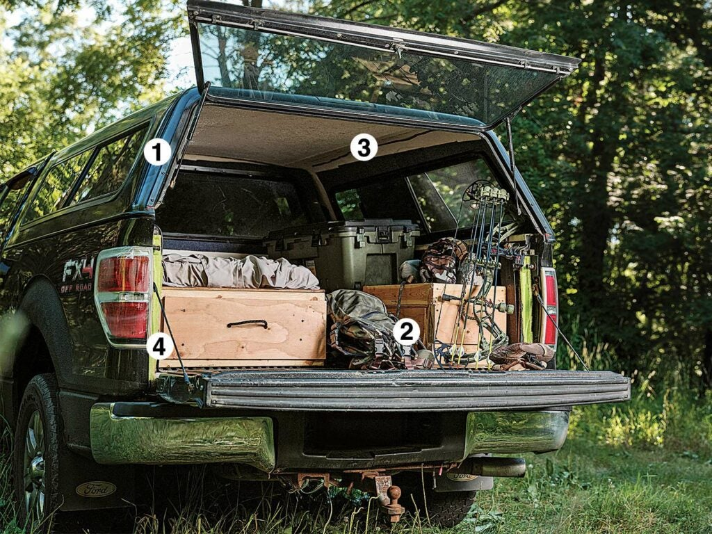a truck bed storage full of hunting gear