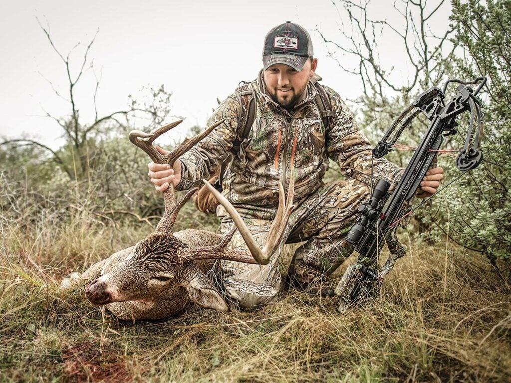 a crossbow hunter kneeling by a buck